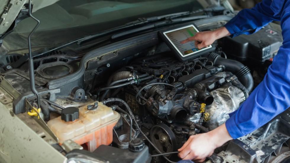 Male mechanic with digital tablet repairing car engine