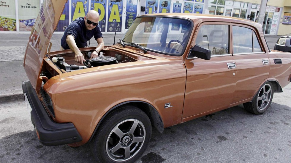 Lester Luis checks a Moskvich in front of Fabian Zakharov's Zakharov Auto Parts shop in Hialeah