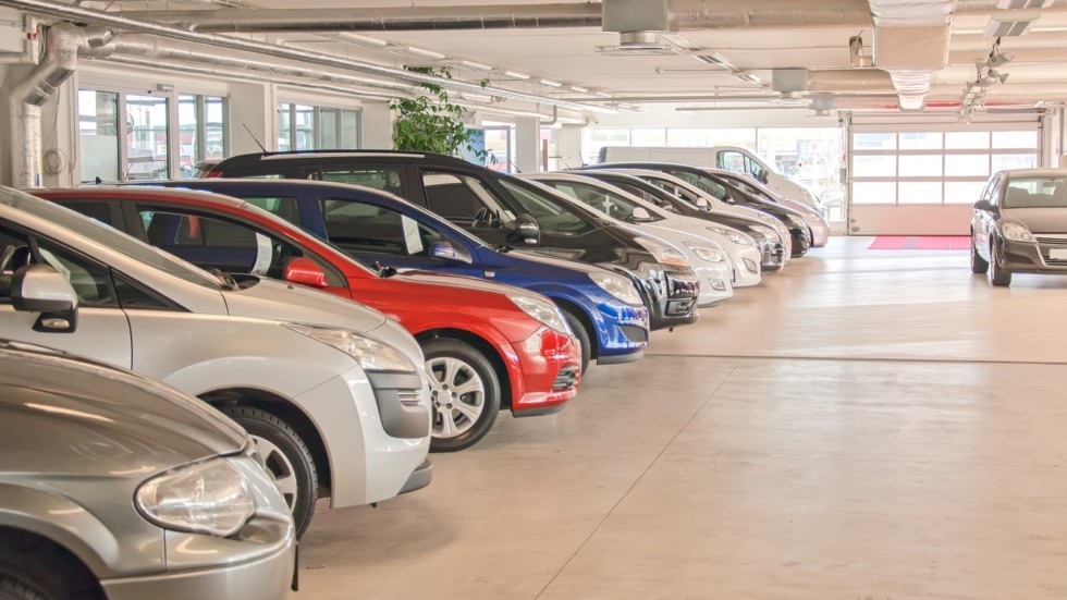 Many cars in parking lot or garage.