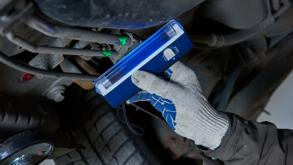 Car air-conditioner servicing. detection freon leak with ultraviolet lamp