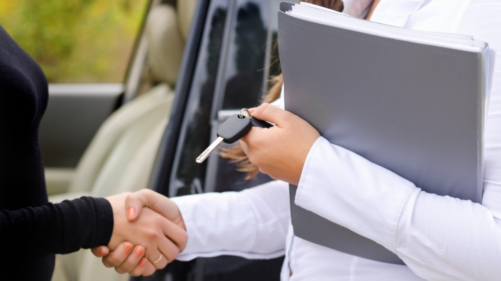 Saleslady selling a car and shaking hands
