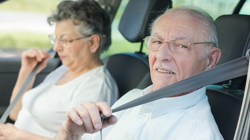 Elderly couple putting on their seatbelts