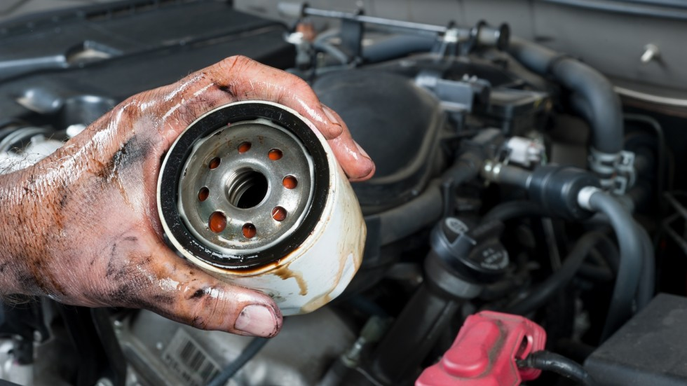Auto mechanic holding oil filter