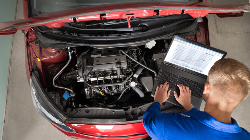 Mechanic Examining Car Engine With Help Of Laptop