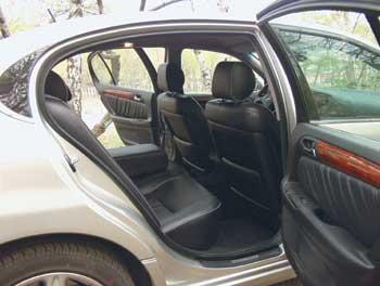 Кожано-деревянная роскошь окружает и задних пассажиров, однако запасом пространства в области ног они не избалованы.